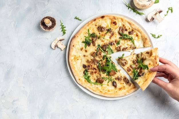Hand nemen van plakjes pizza met mozzarella, champignons en rucola. italiaanse pizza. banner, menu, receptplaats voor tekst, bovenaanzicht.