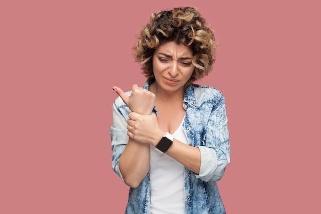 Hand- of polspijn. portret van een zieke jonge vrouw met krullend kapsel in een casual blauw shirt dat haar pijnlijke hand vasthoudt. indoor studio opname, geïsoleerd op roze achtergrond.