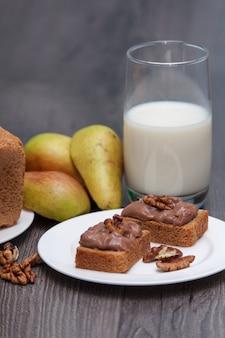 Hand of zelfgemaakte chocoladedeeg met noten. gezonde snack. melk, peren, brood. verticaal.