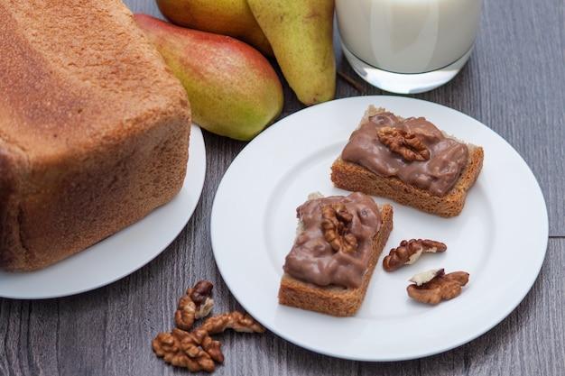 Hand of zelfgemaakte chocoladedeeg met noten. gezonde snack. melk, peren, brood.