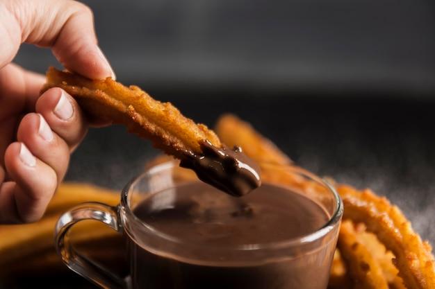 Hand onderdompelen gebraden churros in chocolade