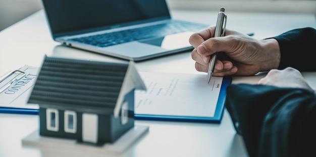 Hand ondertekening van het contract nadat de makelaar het zakelijke contract aan de koper heeft uitgelegd