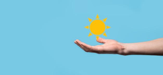 Hand op blauwe achtergrond houdt zon pictogram symbool. duurzame bron van elektriciteit, voeding concept