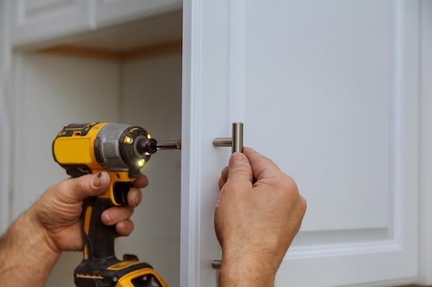 Hand op de deur van de handgreepinstallatie in het keukenkastje met een schroevendraaier