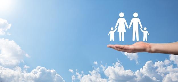 Hand op de hemelachtergrond houdt familiepictogram. gezondheidszorg en levensverzekeringsconcept. vader, moeder, dochter en zoon.