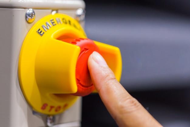 Hand op de rode noodknop of stopknop te drukken. stop-knop, emergeny-stop