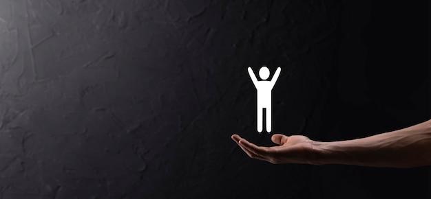 Hand op donkere achtergrond houdt menselijk pictogram vast