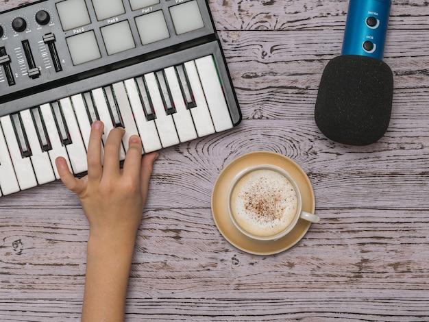 Hand op een muziekmixer, een microfoon en een kopje koffie op een houten tafel