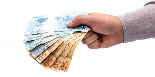Hand op geïsoleerde witte achtergrond die brazilië geld, honderdvijftig reaisbankbiljetten, braziliaanse economie aanbiedt.
