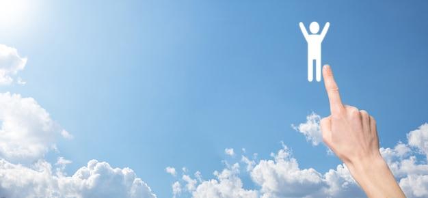 Hand op hemelachtergrond houdt menselijk pictogram vast