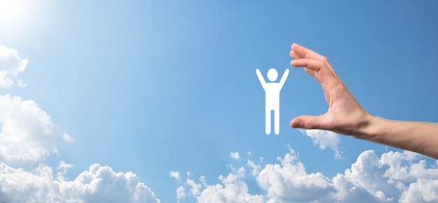 Hand op hemeloppervlak houdt menselijk pictogram