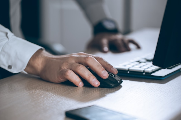 Hand op muis. zakenman computer. zakelijk succes, contract en belangrijk document, papierwerk of advocaat concept. man in het kantoor.