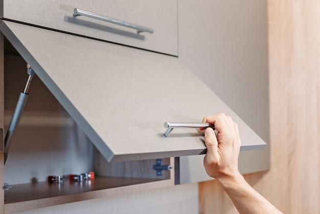 Hand open keukenkast van de mens met handvat