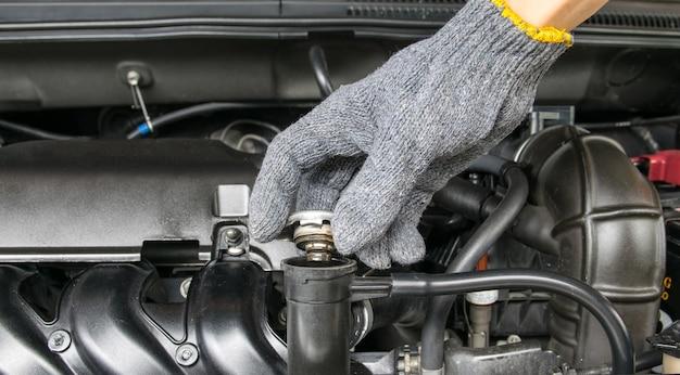 Hand open klep metalen kap op een radiator voor motorkoeling