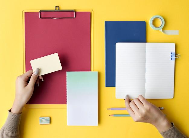 Hand open lege notitieblok en briefpapier op gele achtergrond