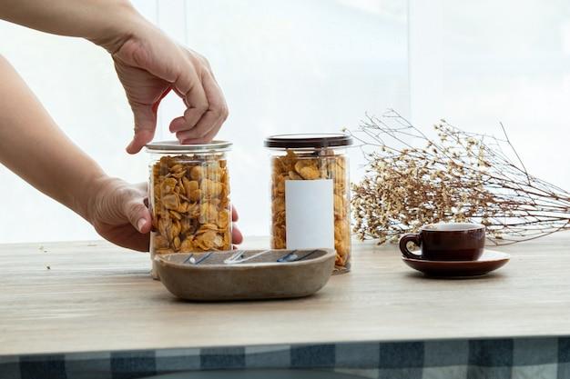 Hand opent het plastic blikje aziatische zoete snacks smakelijke gemengde cornflakes mockup voor logo