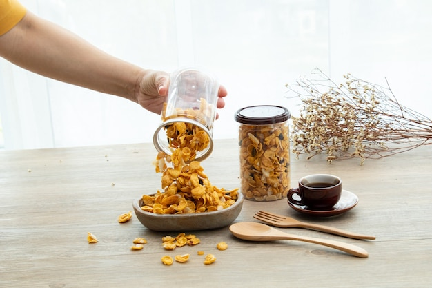 Hand opent het plastic blikje, aziatische zoete snacks, smakelijke gemengde cornflakes, noten, druif en karamel op houten achtergrond natuurlijk licht. verpakken van zoete snacks bij een kopje thee