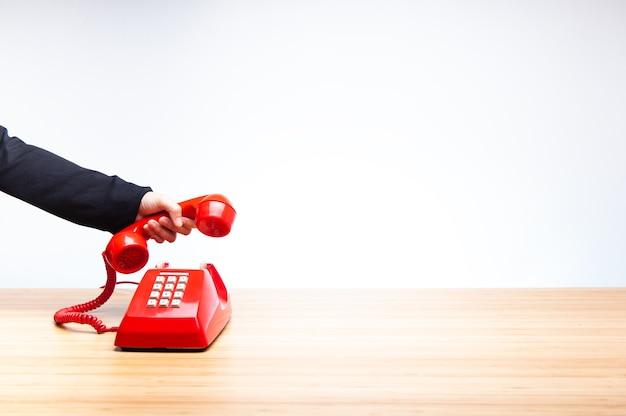 Hand ophangen van rode telefoon