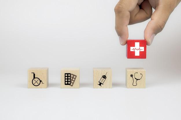 Hand oppakken van gezondheid pictogram op kubus houten speelgoed blokken met andere medische pictogrammen.