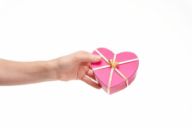 Hand overhandigen van een hartvormige geschenk op witte achtergrond, kopieer ruimte