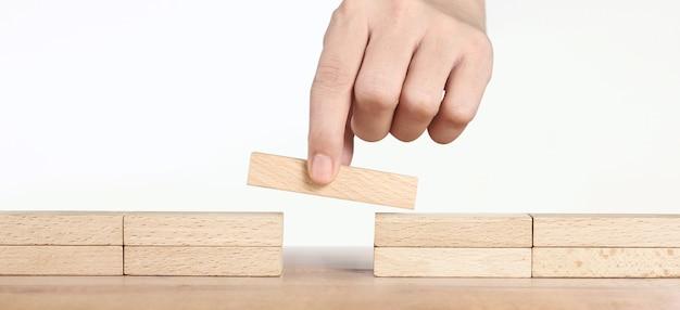 Hand plaatsen van een houten blok, planning van projectbeheer in het bedrijfsleven