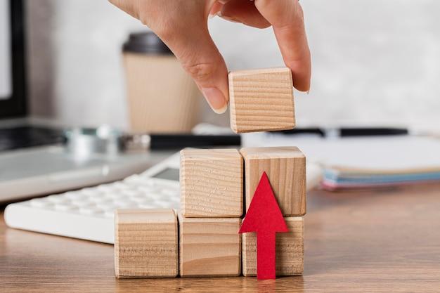 Hand plaatsen van houten blok om groei te vertegenwoordigen