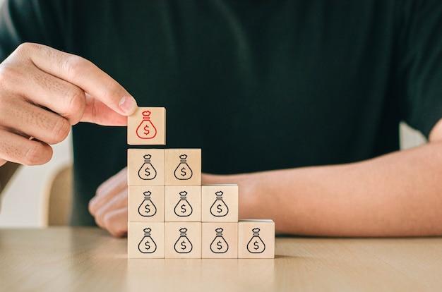 Hand plaatste het houten kubusblok op de piramide van de geldzak. gestapelde houten blokken met geldzakmarkeringen.