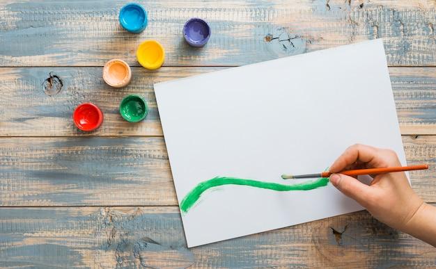 Hand puttend uit wit papier met groene aquarel penseelstreek