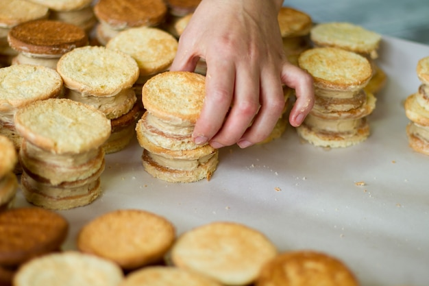 Hand raakt koekjes met room aan. veel gele koekjes. krokant deeg en vla. zoete zelfgemaakte hapjes.