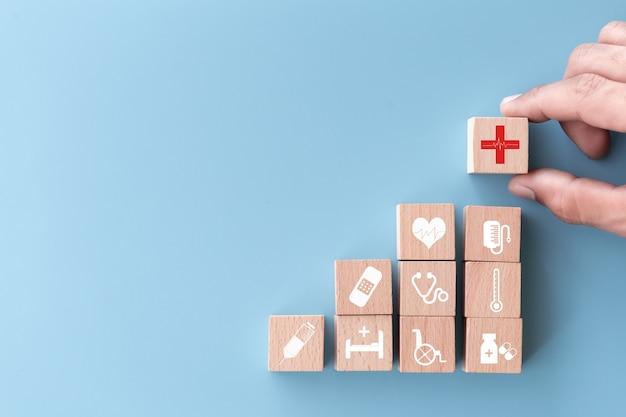 Hand regelen houtblok stapelen met medische pictogram gezondheidszorg
