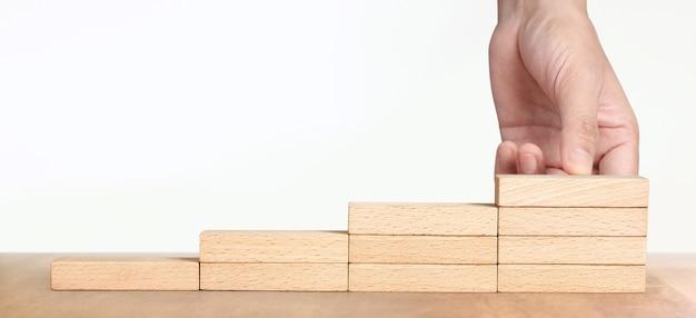 Hand regelen van een houtblok stapelen als stap trap, business concept groeiproces succes