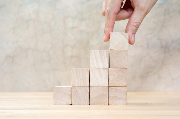Hand regelen van houtblok stapelen als stap trap op houten tafel. bedrijfsconcept voor groeiproces. kopieer ruimte