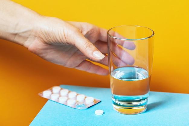 Hand reikt naar een glas water om een pil te drinken