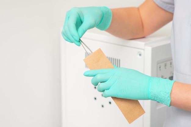Hand reinigt pincet in een ambachtelijke tas. ultrasone reiniger.