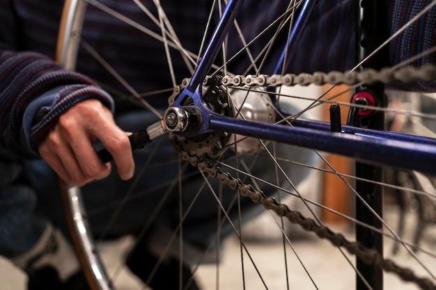 Hand reparatie fiets met moersleutel close-up