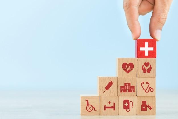 Hand schikken hout blok stapelen met medische pictogram gezondheidszorg.