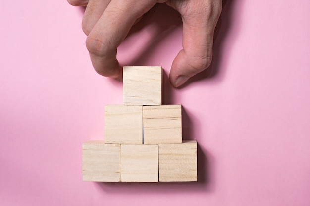 Hand schikken houten kubus stapelen als vorm van de piramide. bedrijfsgroei en managementconcept