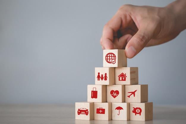 Hand schikken van houtblokken stapelen met pictogram verzekering: auto,
