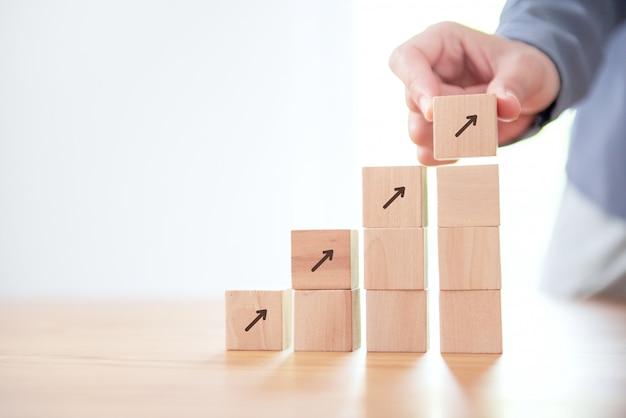 Hand schikken van houten kubus stapelen als stap trap met pictogramgroei.