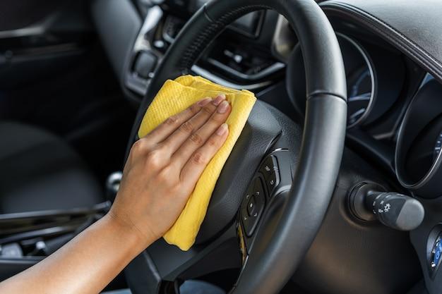 Hand schoonmakend stuurwiel van auto met microfiberdoek