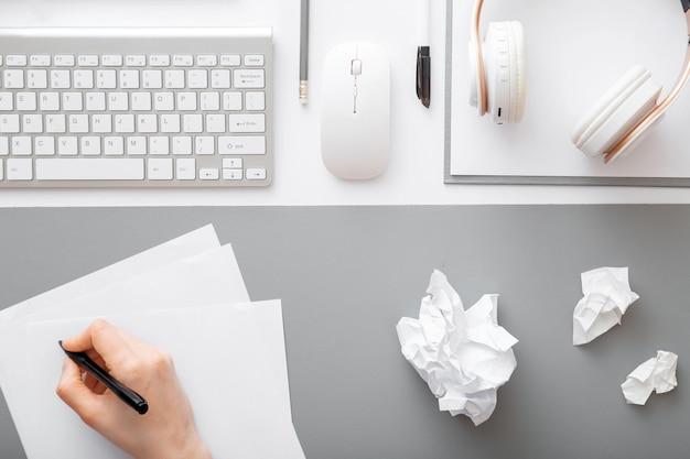 Hand schrijft notities op stuk papier in moderne werkruimte. verfrommeld stukjes papier na het schrijven op een werkend bureau met toetsenbord, koptelefoon muis kantoorbenodigdheden. werkstroom op kantoor aan huis.