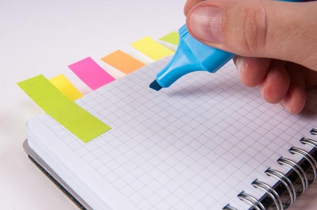 Hand schrijven door blauwe markering op lege kladblok,