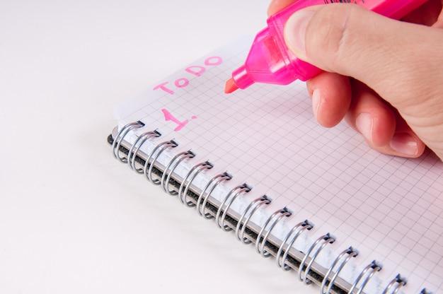 Hand schrijven door roze op lege kladblok,