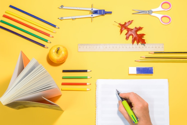 Hand schrijven in een notitieblok op een tafel met schoolbenodigdheden