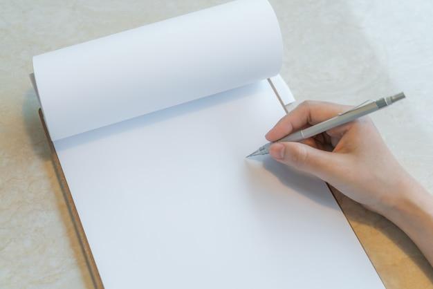 Hand schrijven in een notitieboekje