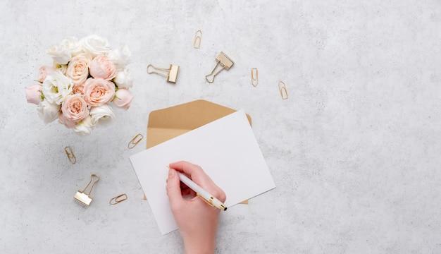 Hand schrijven op een kaart met boeket bloemen en briefpapier