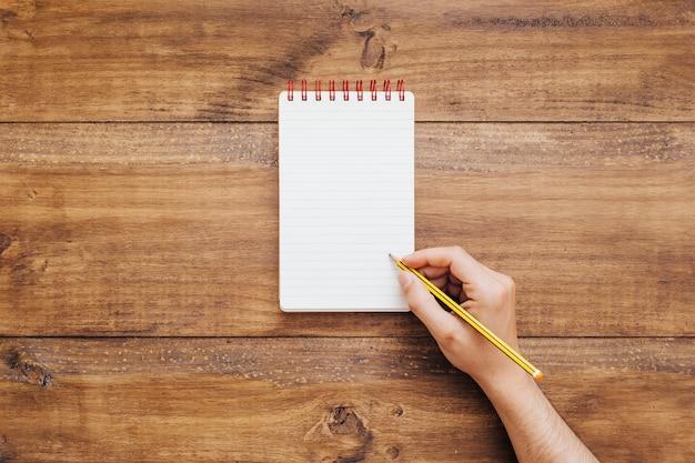 Hand schrijven op kleine kladblok