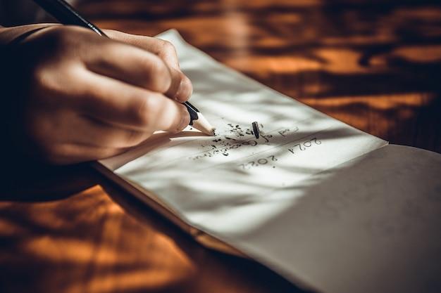 Hand schrijven op wit papier met potlood gebroken