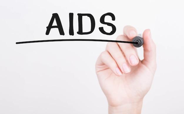 Hand schrijven van aids met zwarte marker op transparante wandbord.