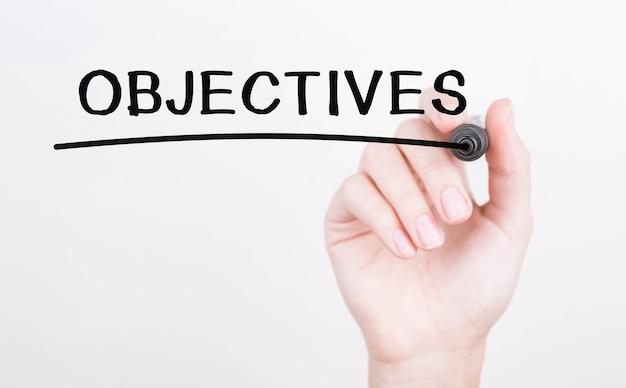Hand schrijven van doelstellingen met zwarte marker op transparante wandbord